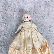 Antique all bisque bonnet head miniature doll in lovely dress