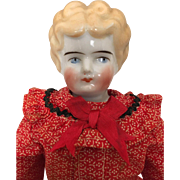 Antique blonde Hertwig lowbrow china doll in festive dress