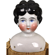 Antique china head doll, lowbrow hairstyle, unusual expression and lovely clothing