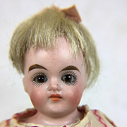Unusual dollhouse girl with blonde hair and glass eyes