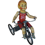Antique lithographed tin toy boy on tricycle