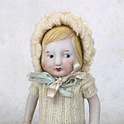Vintage all bisque doll in knit dress and bonnet