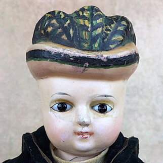 Antique German rare wax-over papier mache boy doll with molded hat and glass eyes.