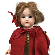 All bisque miniature doll, little girl's face, well-dressed