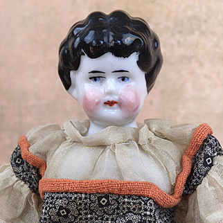 Antique china doll, lowbrow, with pink body and wonderful handmade dress