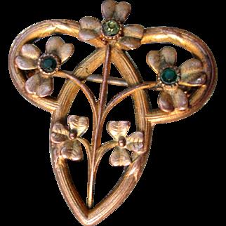 Delicate art nouveau lucky shamrock brooch in brass with green rhinestones, 1900 era