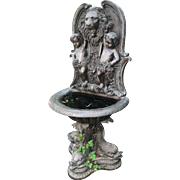 Vintage French bronze fountain and birdbath adorned with cherubs, lion's head and dolphins.