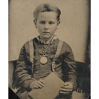 Appealing Tintype of Young Child Wearing a Large Watch or Locket & Holding a Book, late 19th Century