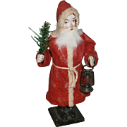German Composition Santa Claus Candy Container Holding a Lantern and Feather Tree Spray