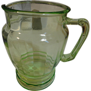 Green Depression glass pitcher has grapes etched  on it
