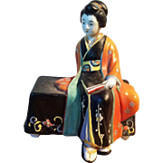 Vintage Japan ceramic porcelain seated lady in a black kimono and orange kimono coat