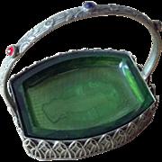 Green crystal salt cellar in jeweled metal holder with carved underside