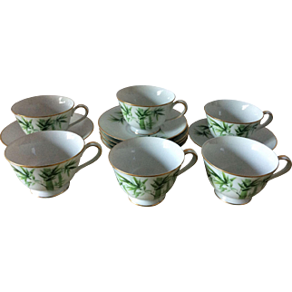 Six vintage Noritake Nippon Toki Kaisha green bamboo design footed cups and saucers with gold rims and handles