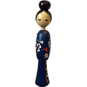 Elegant slender kokeshi in blue kimono with hair bun