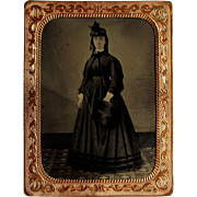 1/4 Tintype of Young Lady- Dark Dress and Muff, Framed in Mat.