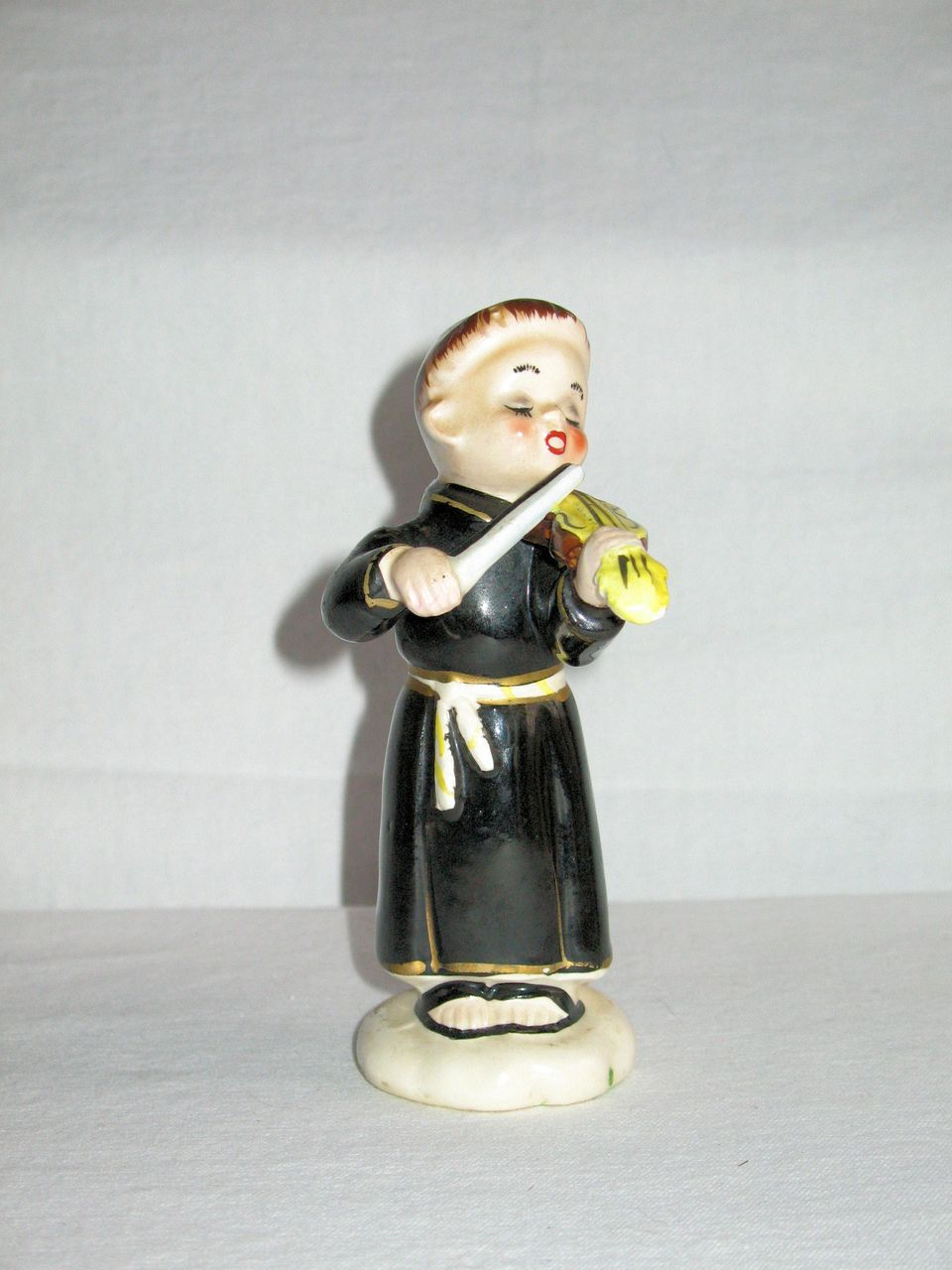 Porcelain Figurine Of A Young Monk Playing A Violin From