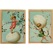 Two Easter Cherubs In Balancing Act With With Eggs
