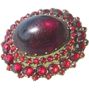 Antique oval shaped Garnet brooch with a Garnet cabochon in the center, 19th century