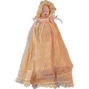 German All Bisque Baby Girl in Christening Gown with Molded Baby Bottle