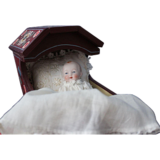 All bisque baby doll/5 inches in length/antique clothing and lying in a wonderfully hand painted Tole cradle