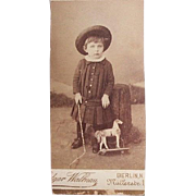 Small boy with toy horse on wheels photo