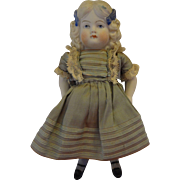 All Bisque Girl with Blonde Molded Hair and Blue Bows