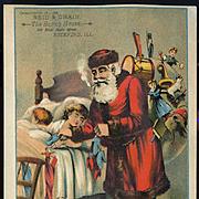 c1890s  Large Victorian Trade Card, Santa Puts Mittens in Sleeping Kids Stockings, Rockford, Illinois