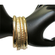 Set Of Four Fourteen Karat Gold Bangle Bracelets With Sliding Clasps