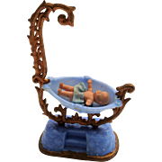 Tiny baby in cradle for dolls house