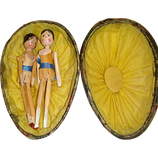 Pair of wooden dolls in silk covered egg