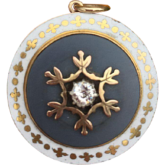 An Antique 15K Gold White and Gold Enamel Mourning Pendant with a diamond set in a grey flat stone and a glass compartment- locket to the back.