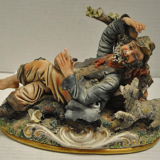 "Lovely Capodimonte Italian Porcelain Reclining Tramp with Dog Figurine 7""H. Folk art style with intricate detailing. Marked with the crown and 125. Measurements: 6.5""D x 11""W x 7""H. One very small chip. Hard to see. (see pic). From a fine non-smoking"
