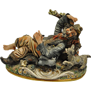 """Lovely Capodimonte Italian Porcelain Reclining Tramp with Dog Figurine 7""""H. Folk art style with intricate detailing. Marked with the crown and 125. Measurements: 6.5""""D x 11""""W x 7""""H. One very small chip. Hard to see. (see pic). From a fine non-smoking"""