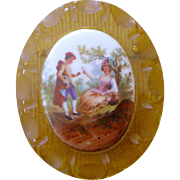 Deco Pin Porcelain Courting Scene Center on Apple Juice Colored Bakelite with Scribed Lines and Deeply Carved Scalloped Oval Rim