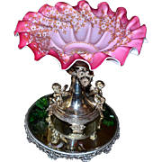 Brides Basket/Centerpiece: Huge Mt Washington Swirl Brides Bowl with Satin Pink Radiating to Deep Coral Pink Embellished with a Profusion of Enamel and Gold Gilded White Flowers Sitting Atop Meriden SP Brides Basket Featuring Two Winged Cherubs
