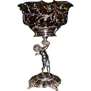 Brides Basket/Centerpiece:  Impressive Amber Enameled Brides Bowl with Teal Blue Rim Attributed to Webb Sitting on Homan Silver Plate Basket Featuring Full Sized Winged Cherub