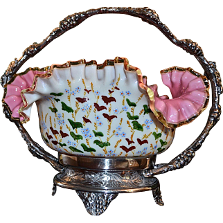 Brides Basket/Centerpiece: Victorian Cased Art Glass Brides Bowl Ruffled and Folded Rim Decorated with Enameled Cherry and Floral Decor Sitting in Pairpoint #4719 SP Basket Featuring Grape/Ivy Decor