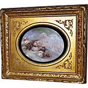 Limoges Oval Hand Painted Porcelain Plaque Of Semi Nude Maiden Reclining Among Apricot, Yellow and Pink Roses in Dramatic Deep Gold Shadow Box Styled Rococo Frame