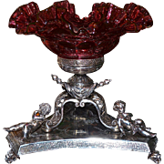 Brides Basket/Centerpiece: Fenton Cranberry Art Glass Crimped and Ruffled Fish Scale Brides Bowl with Scale Design Sitting In Superb Antique James Deakin & Sons Elaborately Detailed Cupid Filled SP Basket