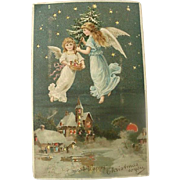Hold To Light Christmas Postcard Angel Hovering Over Town With Christmas Tree In Her Hand