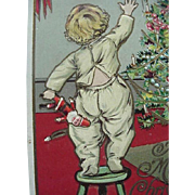 Christmas Embossed Postcard With Boy Standing On Stool With Santa Doll In Hand