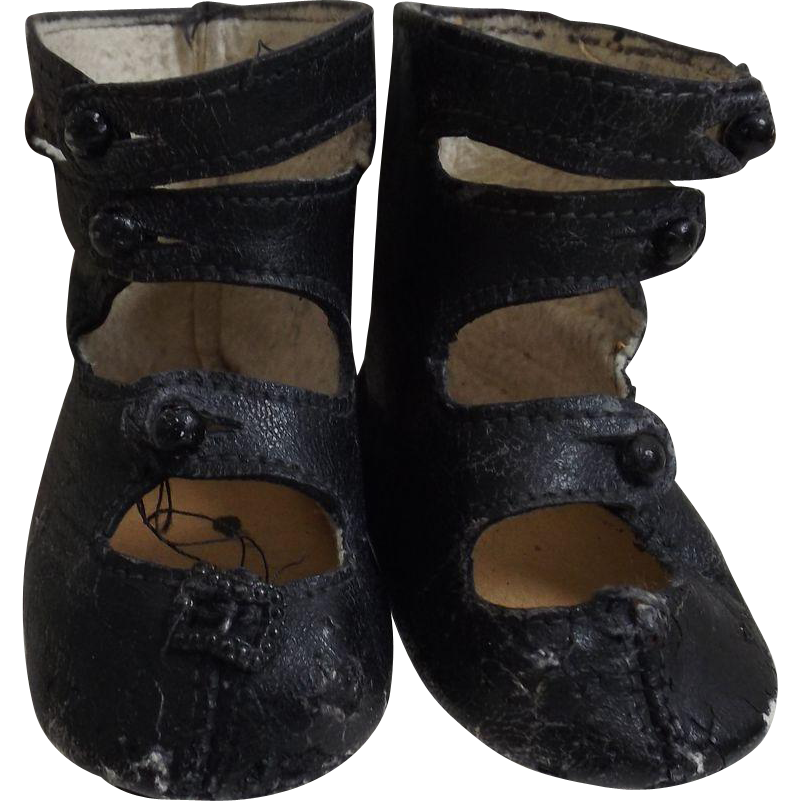 black doll shoes with three straps from