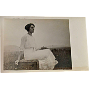 Postcard Woman in White Lacy Dress Sitting on a Wood Box RPPC