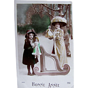 Two Beautiful Girls with Dolls, Happy New Year, Hand Tinted French Real Photo Postcard Dated 1910