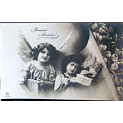 French Christmas Card, Two Little Angels Deliver a Doll and Gifts, Real Photo Postcard, Circa 1910s