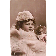 German Tinted Real Photo Postcard, Little Girl and Pretty Doll Wrapped in Fur, Circa 1910s