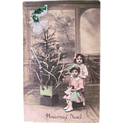 Hand Tinted French Real Photo Postcard, Little Boy and Girl With Doll and Christmas Tree, Circa 1910s