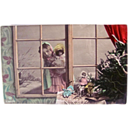 German Tinted Real Photo Postcard, Little Girl and Doll Peeking Through a Window, Christmas Card, Circa 1910s