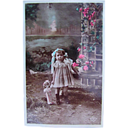 French Tinted Real Photo Postcard, Little Girl and Doll Taking a Walk Under the Roses, Circa 1910s