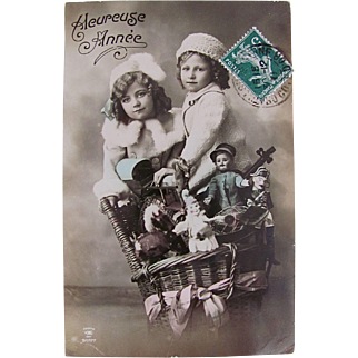 Hand Tinted French Real Photo Postcard, 2 Children With Basket of Dolls and Toys, Heureuse Année, Postmarked 1911